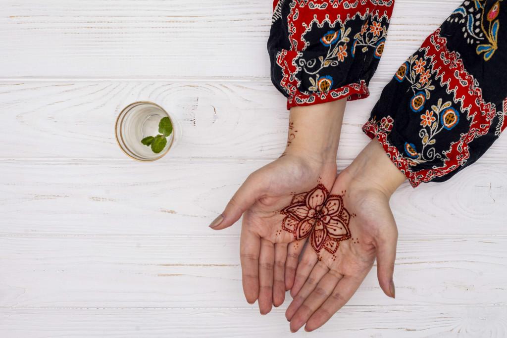 woman applying mehendi on her hands