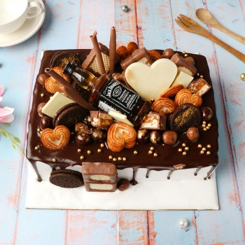 One Kg Chocolate Cream Cake Topped with Oreo Biscuits,Heart Cookies,Snicker Chocolate,Brookside chocolate,milky bar chocolate,strawberry cream wafers and Jack Daniel Miniature Bottle