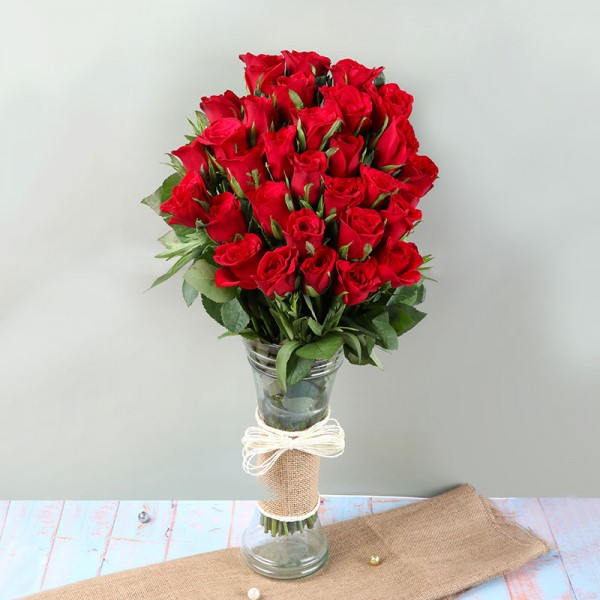 An arrangement of 30 Red Roses in a Glass Vase