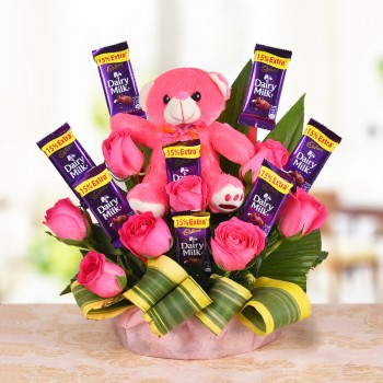 A Basket Arrangement of 8 Pink roses and 8 Cadbury's Dairy Milk of 13 gms each with Teddy bear (6 Inches) with dracaena leaves
