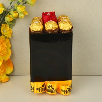 Arrangement of 8 ferrero rochers with A red rose having pearl inside in Black glass vase