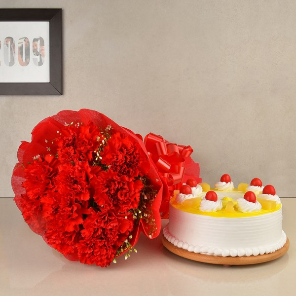 12 Red Carnations wrapped in crape paper with Half Kg Pineapple Cake