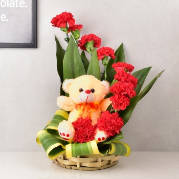 12 Red Carnations arranged in a basket with Teddy Bear (6 inches)