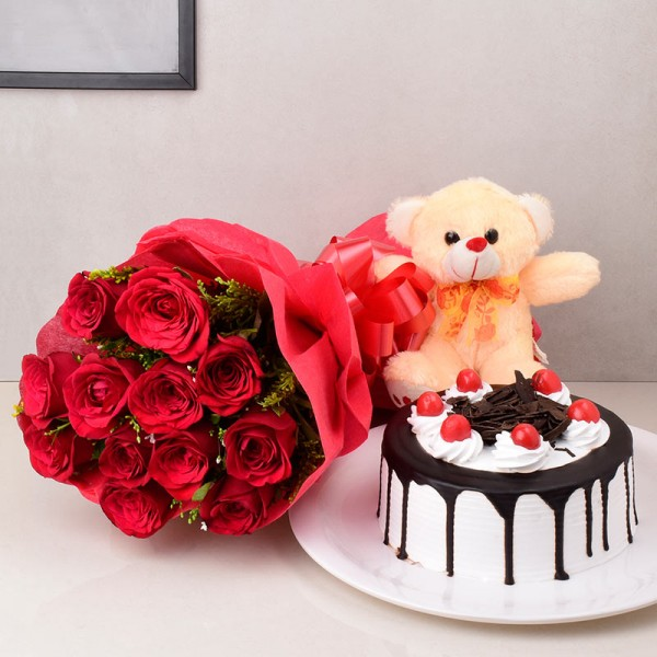 12 Red Roses in Paper Packing with Half Kg Black Forest Cake and Teddy bear (6 Inch)
