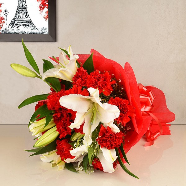 12 Red Carnations and 4 White Asiatic Lilies in Paper packing