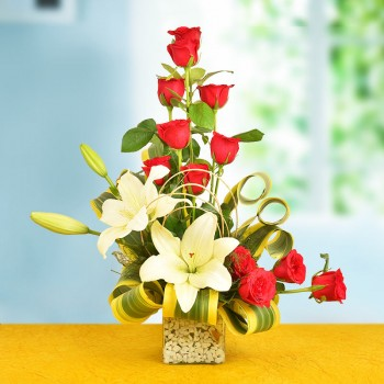 A Floral Arrangement of 12 Red Roses and 2 White Asiatic Lilies in a glass vase