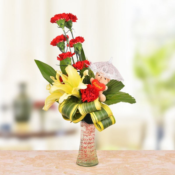 Floral Arrangement of 8 Red Carnations, 2 Yellow Asiatic Lilies and a 3 Inches Brown Teddy Bear with dracaena leaves
