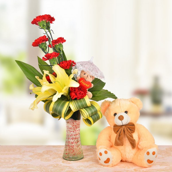Floral Arrangement of 8 Red Carnations, 2 Yellow Asiatic Lilies and a 3 Inches Brown Teddy Bear with dracaena leaves in a Glass Vase with 1 Brown Teddy Bear (12 Inches)
