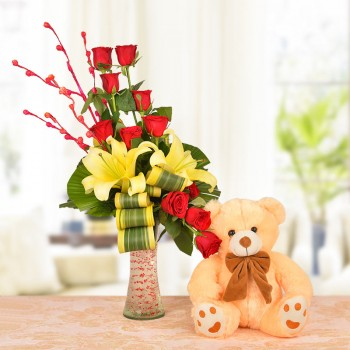 Floral Arrangement of 8 Red Roses, 2 Yellow Asiatic Lilies with dracaena leaves in a Glass Vase with 1 Brown Teddy Bear (12 Inches)