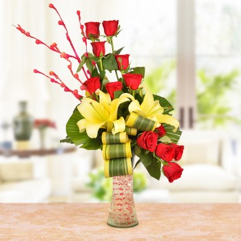 Floral Arrangement of 8 Red Roses, 2 Yellow Asiatic Lilies with dracaena leaves in a Glass Vase
