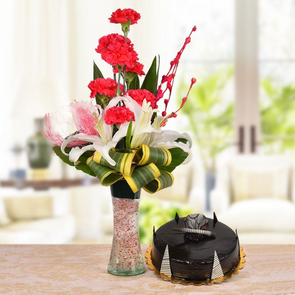 Floral Arrangement of 8 Red Carnations, 2 White Lilies with dracaena leaves in a Glass Vase with Half Kg Chocolate Truffle Cake