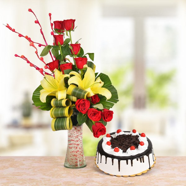Floral Arrangement of 8 Red Roses, 2 Yellow Asiatic Lilies with dracaena leaves in a Glass Vase with Half Kg Black Forest Cake