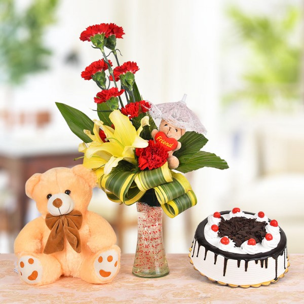 Floral Arrangement of 8 Red Carnations, 2 Yellow Asiatic Lilies and a 3 Inches Brown Teddy Bear with dracaena leaves in a Glass Vase a Brown Teddy Bear (12 Inches) and Half Kg Black Forest Cake