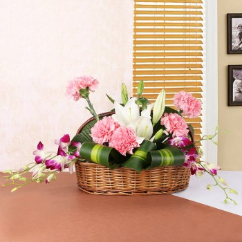2 White Asiatic Lilies, 5 Pink Carnations, 4 Purple Orchids in Handle Basket