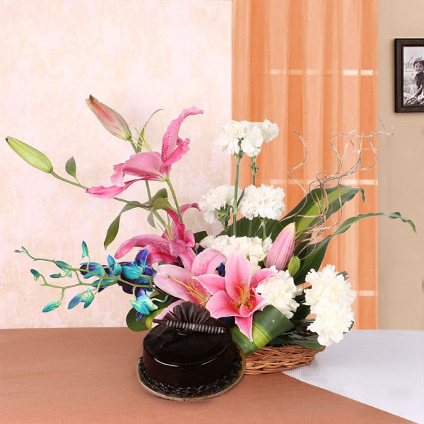 Floral Arrangement of 4 Pink Asiatic Lilies, 10 White Carnations and 2 Blue Orchids in a Basket with Half Kg Chocolate Truffle Cake