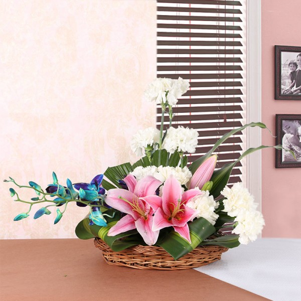 2 Pink Asiatic Lilies, 10 White Carnations and 2 stems of Blue Orchid in a Basket