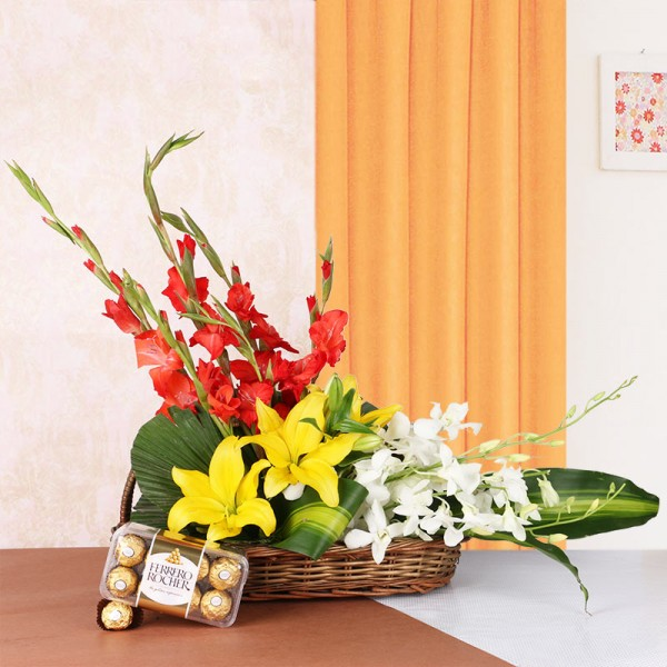Floral Arrangement is the best gift ever. It has 3 Yellow Asiatic Lilies, 4 Red Glads and 3 White Orchids in a Basket with a box of 16 pcs of Ferrero Rocher Chocolates