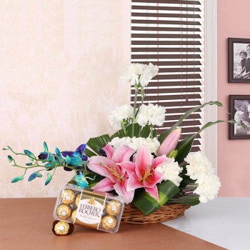 Floral Arrangement like this one. It includes 2 Pink Asaitic Lilies, 10 White Carnations and 2 stems of Blue Orchid in a Basket with a box of 16 pcs of Ferrero Rocher Chocolates