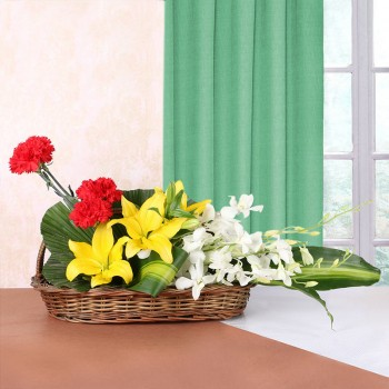 3 Yellow Asiatic Lilies, 4 Red Carnations, 4 White Orchids in Handle Basket