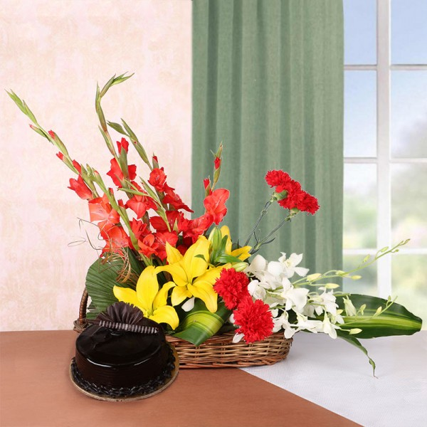 Floral Arrangement of 3 Yellow Asiatic Lilies, 4 Red Glads, 4 Red Carnations and 2 White Orchids in a Basket with Chocolate Truffle Cake (Half Kg)