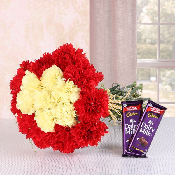 16 Carnations (Yellow and Red) in Yellow Raffia Knot with 2 Cadbury Dairy Milk Chocolates (25gms each)