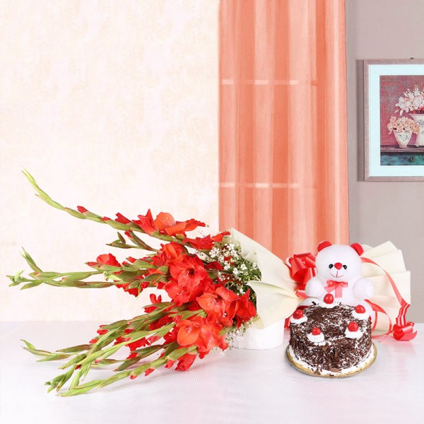 10 Red Glads in White Packing paper with Black Forest Cake (Half Kg) and Teddy Bear (6 inches)