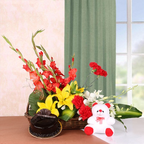 Floral Arrangement of 3 Yellow Asiatic Lilies, 4 Red Glads, 4 Red Carnations and 2 White Orchids in a Basket with Chocolate Truffle Cake (Half Kg) and Teddy Bear (6 inches)