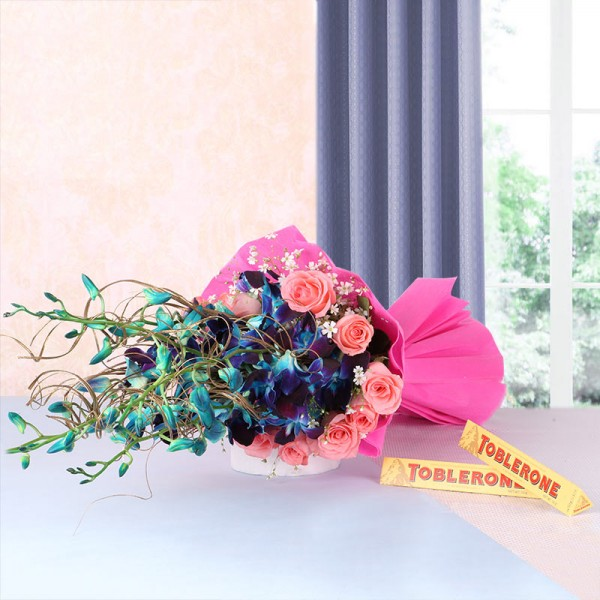 6 Blue Orchids and 12 Pink Roses in Pink Paper packing with 2 Toblerone Chocolates (50gms each)