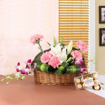 Floral arrangement of 2 White Asiatic Lilies, 5 Pink Carnations, 4 Purple Orchids in Handle Basket with a box of 16 pcs of Ferrero Rocher Chocolates