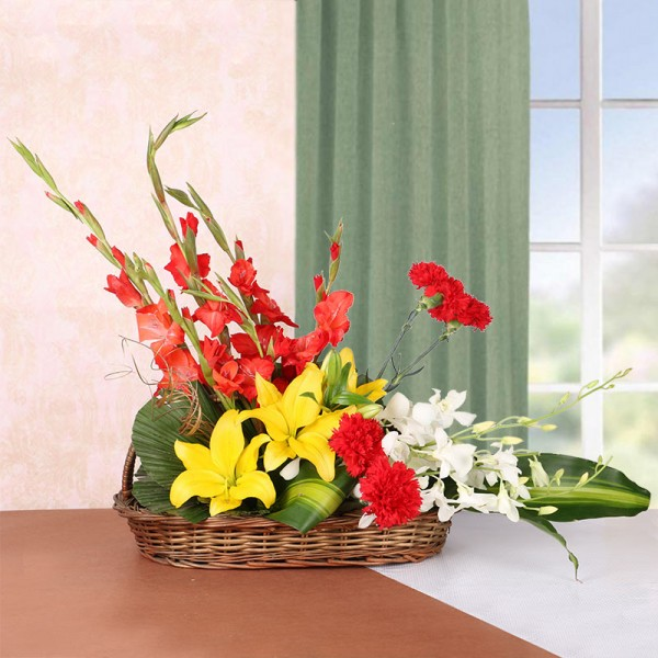 Floral Arrangement of 3 Yellow Asiatic Lilies, 4 Red Glads, 4 Red Carnations and 2 White Orchids in a Basket