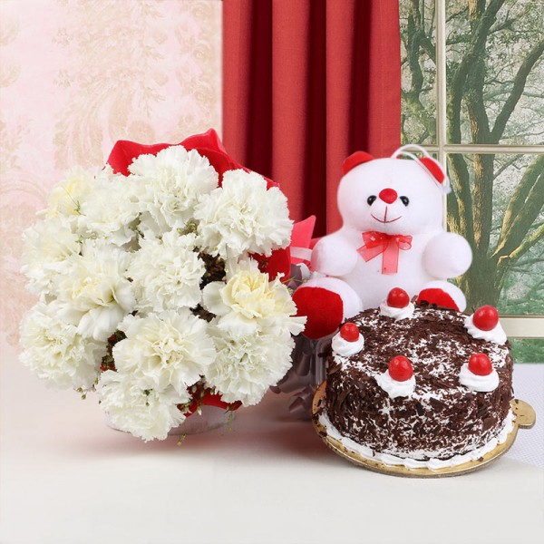 12 White Carnations in Red Paper Packing with Black Forest Cake (Half Kg) and Teddy Bear (6 inches)