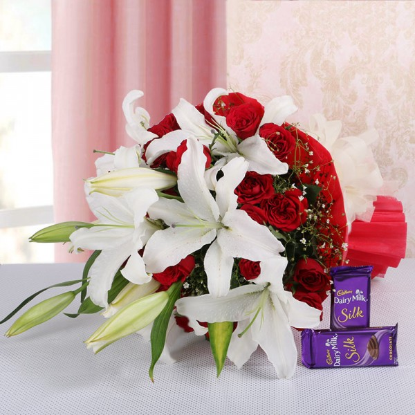 4 White Asiatic Lilies and 15 Red Roses in Red paper, White paper bow with 2 Cadbury's Silk (60gms each)