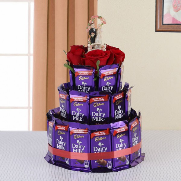 Cake arrangement of 30 Dairy Milk Chocolates (13gms each) with 5 Red Roses and 1 Couple Statue