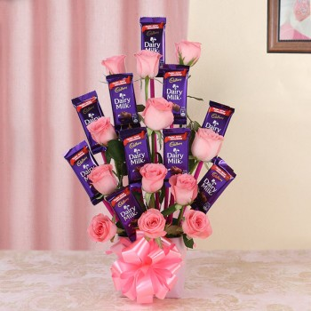 Arrangement of 12 Pink Roses and 10 Dairy Milk Chocolates (13gms each) in Glass Vase