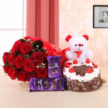 10 Red Roses in Paper Packing with 2 Cadbury's Dairy Milk Silks and Black Forest Cake (Half Kg) and 1 Teddy Bear (6 Inches)
