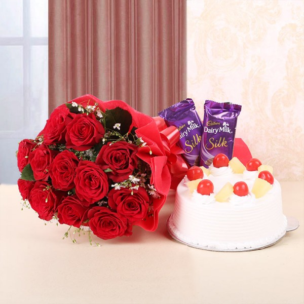 12 Red Roses in Red Bow and Red Paper with Pineapple Cake (Half Kg) and 2 Cadbury's Dairy Milk Silk (60gms each)