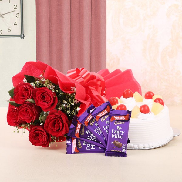 6 Red Roses in Red Paper with Pineapple Cake (Half Kg) and 5 Cadbury's Dairy Milk (13gms each)