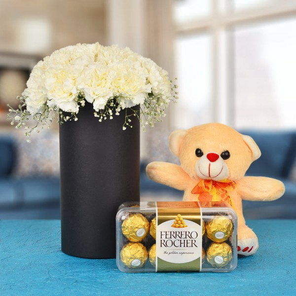 20 White Carnations In A Black Cylindrical Vase with 16 pcs Ferrero Rocher and 1 Teddy (6 Inches)