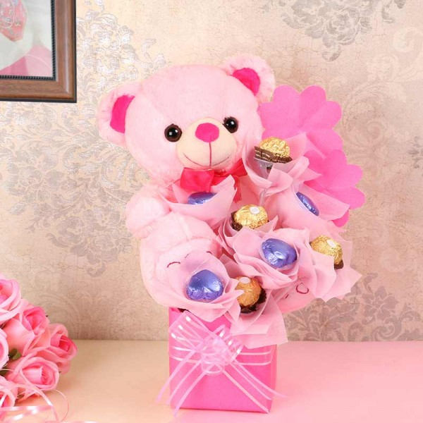 An arrangement of 1 Teddy Bear( 10 inches), 4 round-shaped assorted chocolates, 4 heart-shaped assorted chocolates in a vase