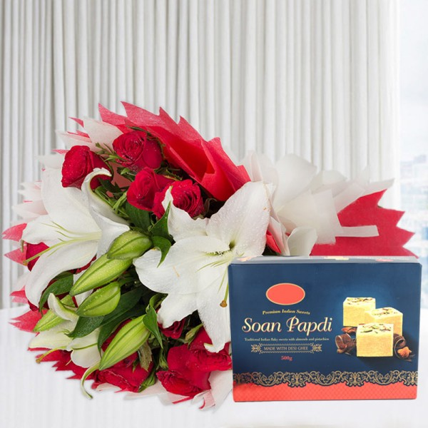 A bunch of Flowers (12 Red Roses, 3 White Asiatic Lily) in Red and White Paper Packing, White Paper Bow with Soan Papdi (Half Kg)