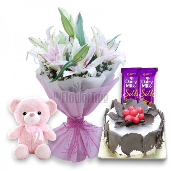 6 Oriental Lilies with 2 Cadbury's DairyMilk Silk, Half Kg Black Forest Cake, Teddy Bear (6 inches) and Paper Packing