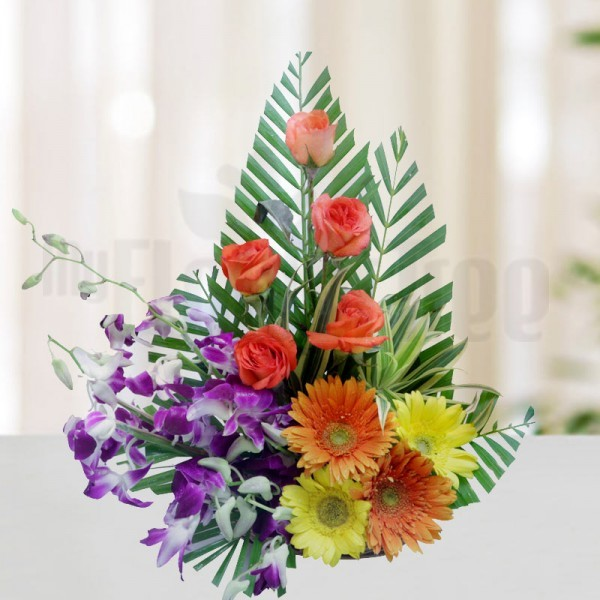 5 Orange Roses and 4 Yellow Gerberas and 3 Purple Orchids with Arica Palm Leaves in a Basket