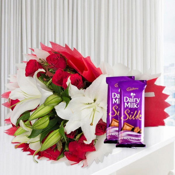 A bunch of Flowers (12 Red Roses, 3 White Asiatic Lily) in Red and White Paper Packing, White Paper Bow with 2 Cadbury's DairyMilk Silk (60gms each)