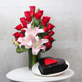 20 Red Roses and 3 Asiatic Pink Lilies with Glass Vase Arrangement and Half Kg Heart Shape Chocolate Cake