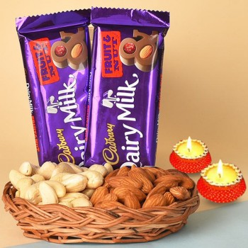 A Cane Basket containing Almonds (100 gms) and Cashew Nuts (100 gms) with 2 Cadbury Dairy Milk Fruit N Nut Chocolates (38 gms each) and Set of 2 Diya for Diwali