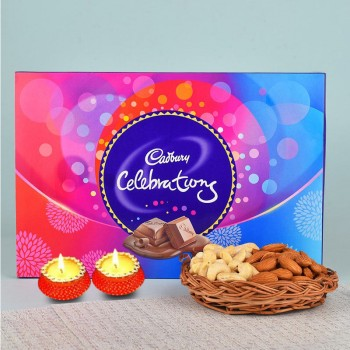 A Cane Basket containing Almonds (100 gms) and Cashew Nuts (100 gms) with 1 Cadbury Celebrations Pack (131.3 gms) and Set of 2 Diya for Diwali
