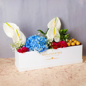 4 White Anthurium Flowers,1 Blue Hydrangea,1 Green Berries,4 Red Carnations,12 pcs of Ferrero Rocher Chocolate arrangement in MFT White Rectangular Box