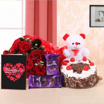 10 Red Roses in Paper Packing with 2 Cadbury's Dairy Milk Silks and Black Forest Cake (Half Kg) and 1 Teddy Bear (6 Inches) also a Valentines Day Greeting Card