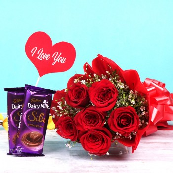"6 Red Roses in Paper Packing and 2 Dairy Milk Silk Chocolate (65 gm) with ""I love you"" Tag"